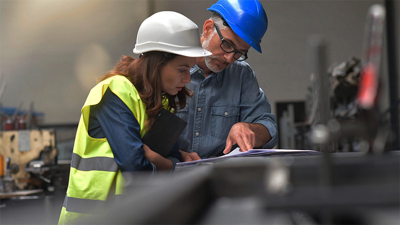 Man and woman wearing hard hats and looking at documents
