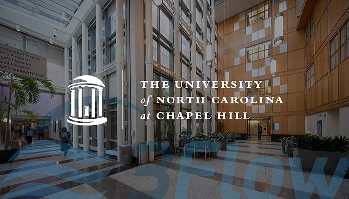 UNC logo over darkened photo of their building lobby